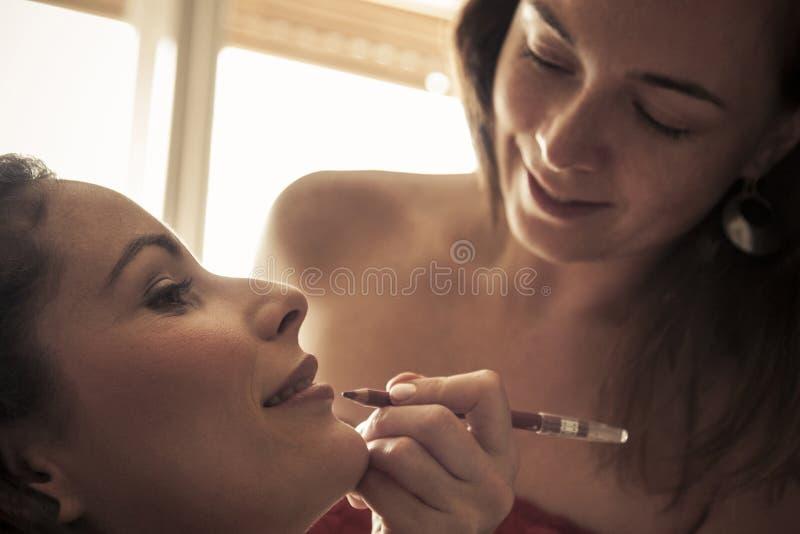 Jonge mooie vrouwen die samenstelling toepassen stock afbeeldingen