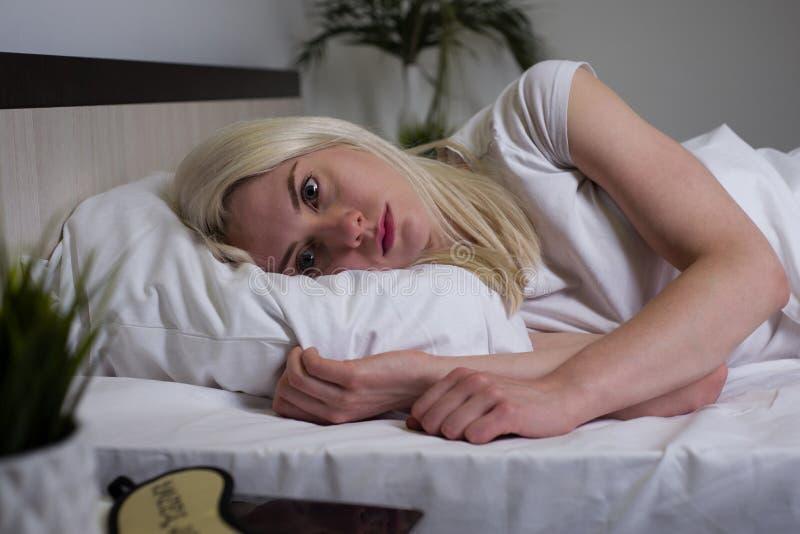 Jonge mooie vrouwen thuis slaapkamer die in bed laat bij nacht liggen die aan slaap proberen die aan de wanorde van de slapeloosh stock foto's