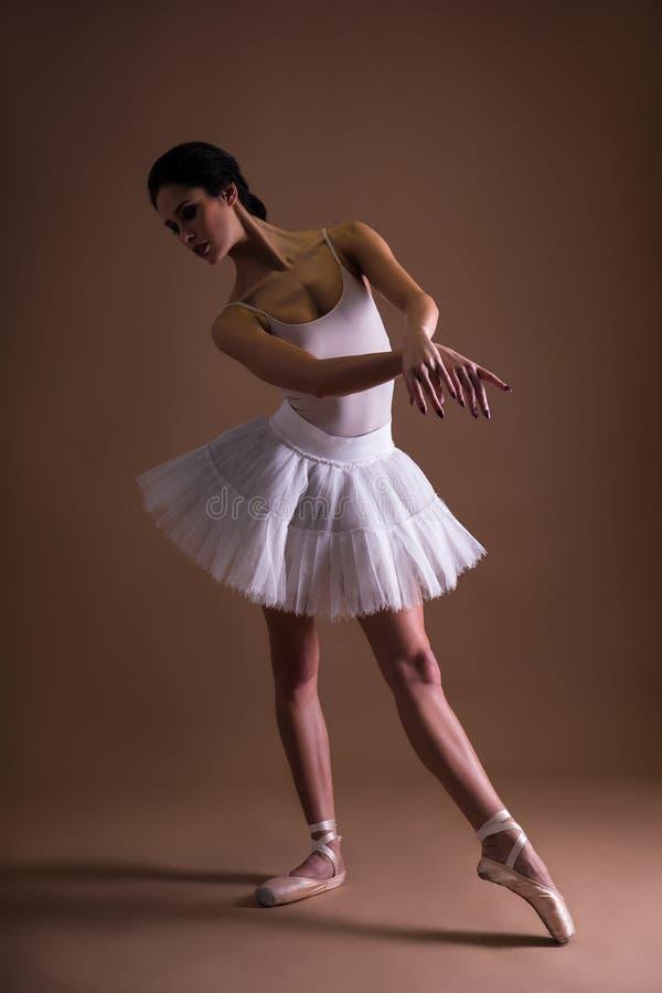 Jonge mooie vrouwenballerina in tutu het stellen over beige stock foto's