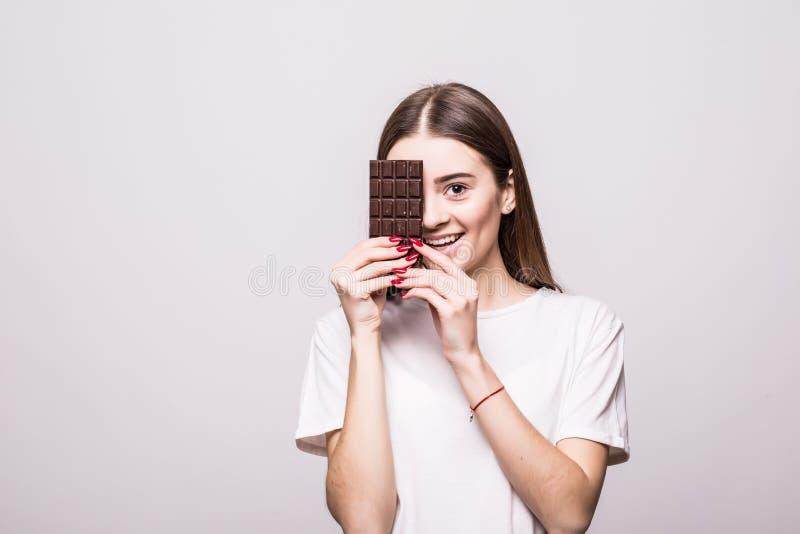 Jonge mooie vrouwenbeten van plak van chocoladereep op witte achtergrond Het concept van de gezondheid royalty-vrije stock fotografie