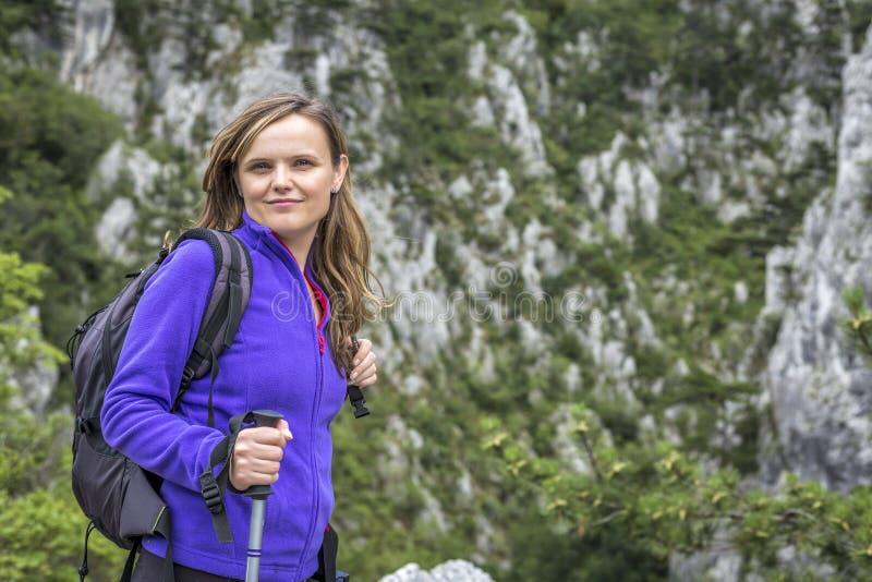 Jonge mooie vrouwenholding wandelingspool terwijl het beklimmen van ro royalty-vrije stock fotografie
