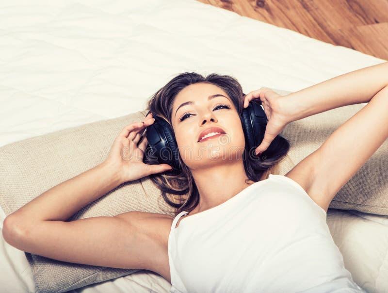 Jonge mooie vrouwenhoofdtelefoons het luisteren muziek op bed stock fotografie