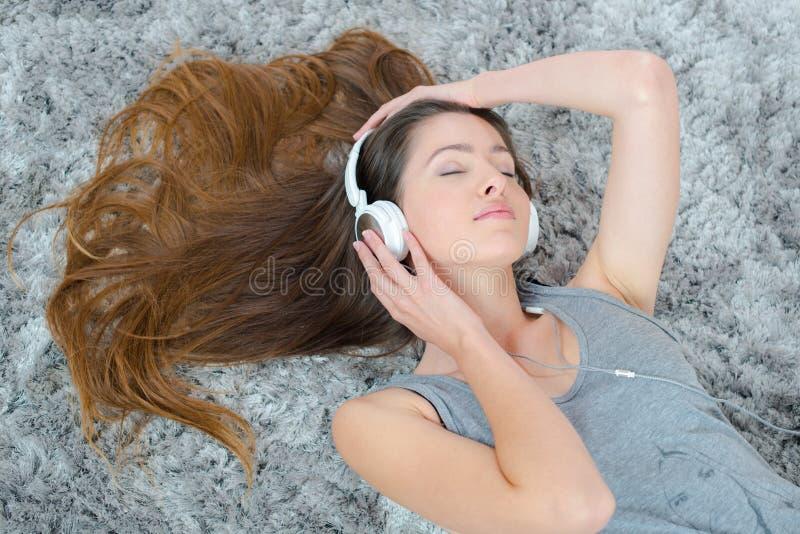 Jonge mooie vrouwenhoofdtelefoons het luisteren muziek op vloer royalty-vrije stock foto