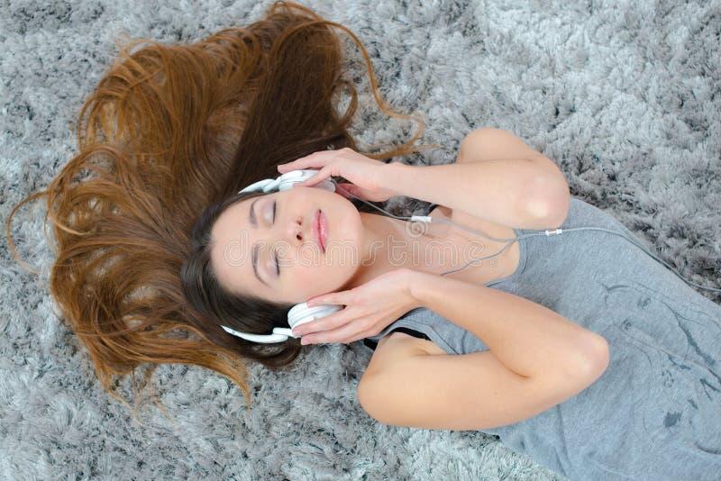 Jonge mooie vrouwenhoofdtelefoons het luisteren muziek op vloer stock foto's