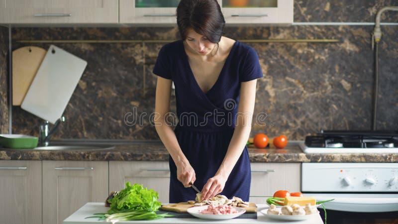 Jonge mooie vrouwenkok die de paddestoelen op houten raad voor pizza in de keuken thuis snijden stock foto's