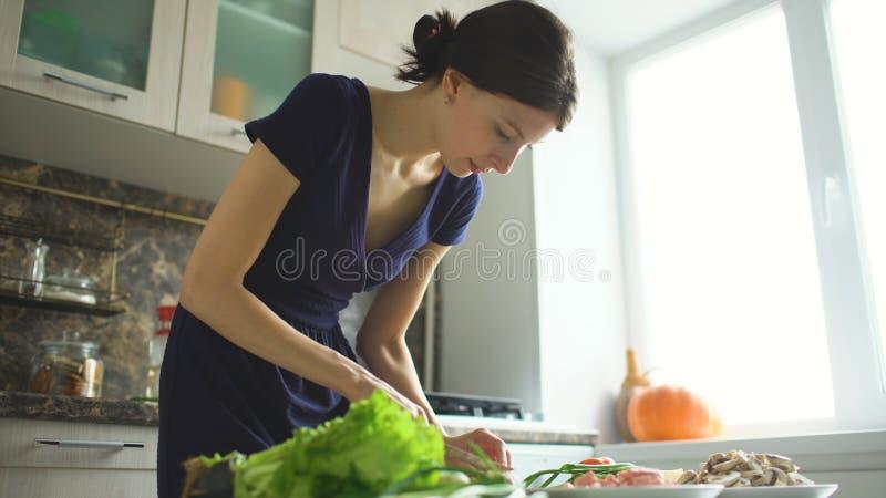 Jonge mooie vrouwenkok die de paddestoelen op houten raad voor pizza in de keuken thuis snijden royalty-vrije stock afbeelding