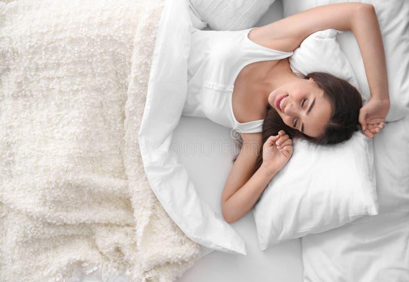 Jonge mooie vrouwenontwaken na het slapen in bed stock afbeeldingen