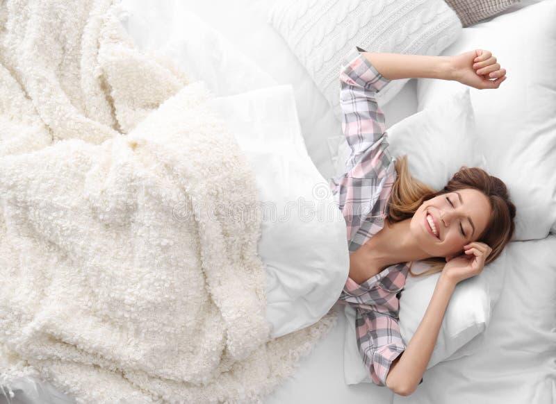 Jonge mooie vrouwenontwaken na het slapen in bed stock foto's