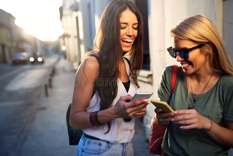 Jonge mooie vrouwenvrienden die in de straat met telefoon stellen stock foto's