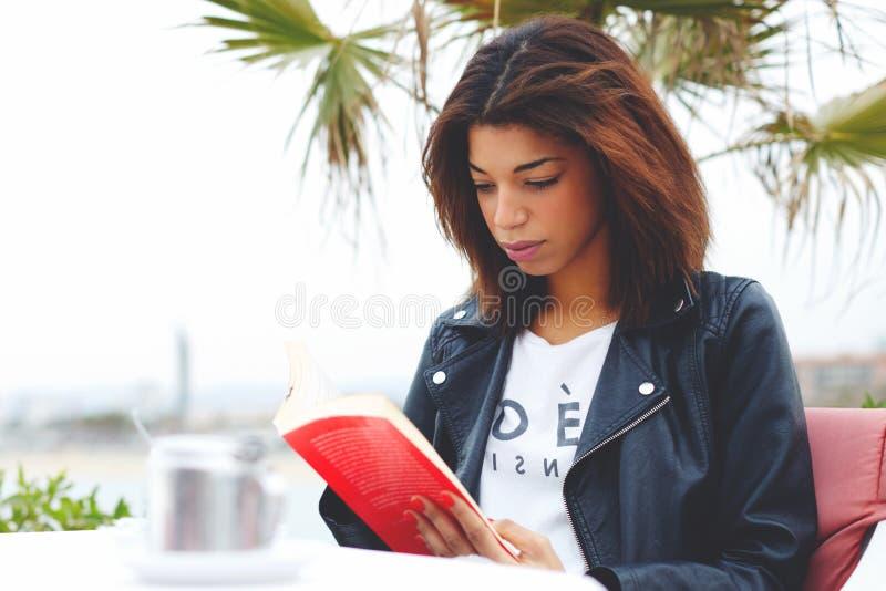 Jonge mooie vrouwenzitting bij van de het terras peinzende lezing van de koffiewinkel het interessante boek royalty-vrije stock fotografie
