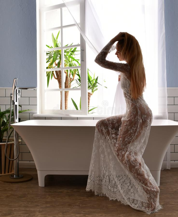 Jonge mooie vrouwenzitting dichtbij badkuip klaar voor dichtbij het nemen van bad royalty-vrije stock fotografie