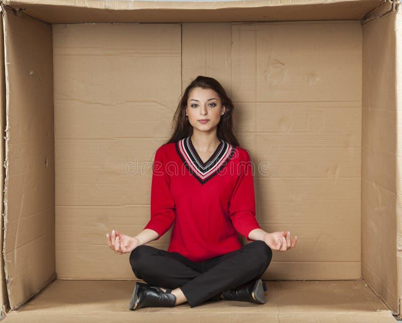 Jonge mooie vrouwenzitting in een kartonbespreekbureau stock afbeelding