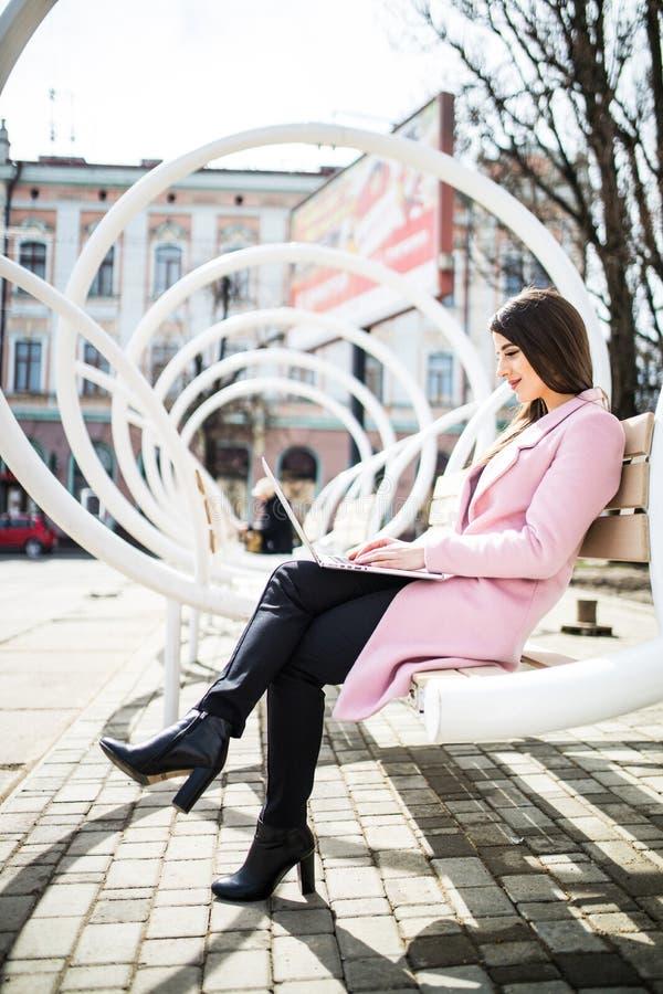 Jonge mooie vrouwenzitting en het ontspannen op de straat moderne bank en gebruikend laptop stock afbeelding