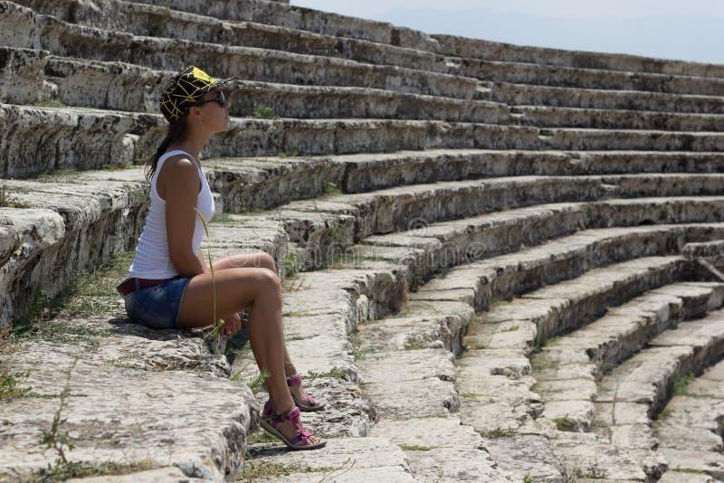 Jonge mooie vrouwenzitting in het amfitheater royalty-vrije stock foto