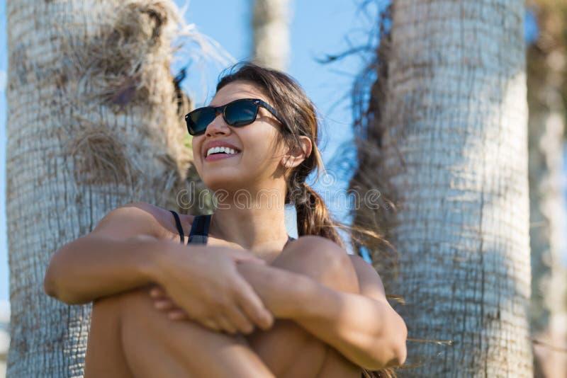 Jonge mooie vrouwenzitting met het gekruiste benen glimlachen stock foto