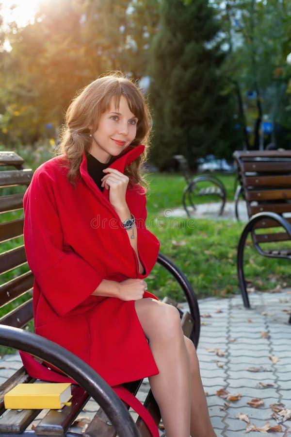 Jonge mooie vrouwenzitting op een bank in de herfstpark royalty-vrije stock foto's