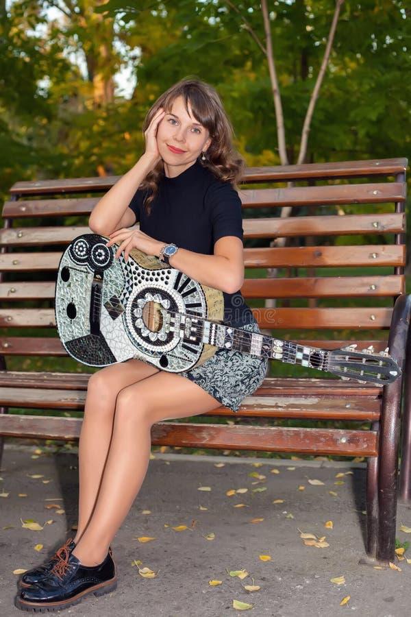 Jonge mooie vrouwenzitting op een bank die de gitaar spelen royalty-vrije stock foto's
