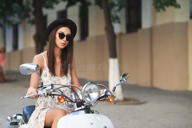 Jonge mooie vrouwenzitting op een Italiaanse autoped royalty-vrije stock foto's