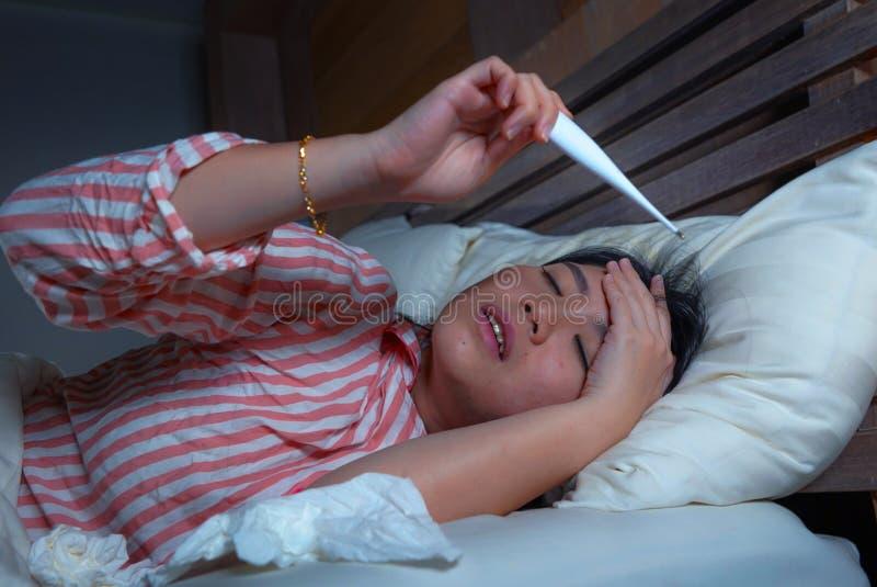 Jonge mooie zieke en uitgeputte Aziatische Chinese vrouw die koude en griep van de holdingspapieren zakdoekje en thermometer aan  stock afbeelding