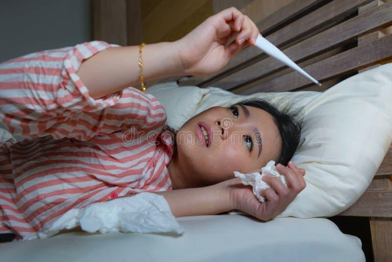 Jonge mooie zieke en uitgeputte Aziatische Koreaanse vrouw die koude en griep van de holdingspapieren zakdoekje en thermometer aa stock foto's