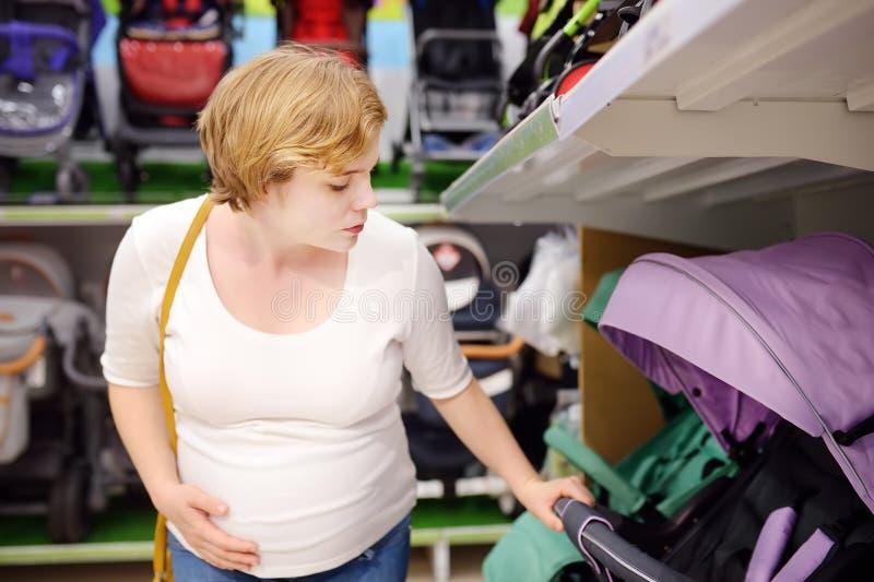 Jonge mooie zwangere vrouw babywandelwagen kiezen of kinderwagen die met fouten voor pasgeboren Het winkelen voor aanstaande moed stock foto's