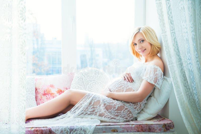 Jonge mooie zwangere vrouwenzitting op vensterbank thuis royalty-vrije stock afbeelding