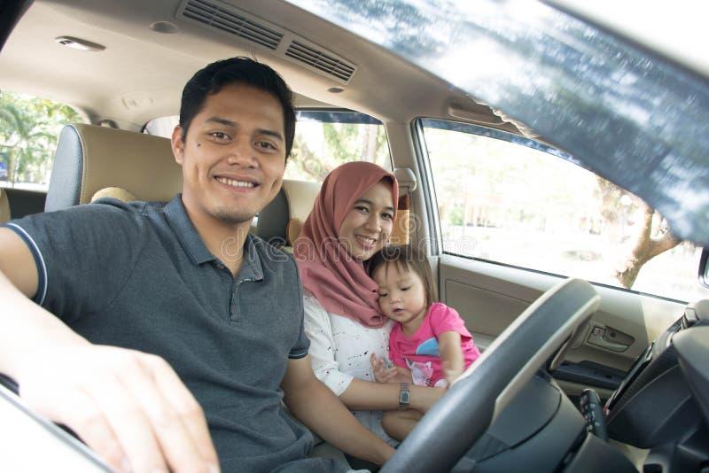 Jonge moslimfamilie, vervoer, vrije tijd, wegreis en mensenconcept - gelukkig man, vrouw en meisje die binnen een auto reizen stock foto's