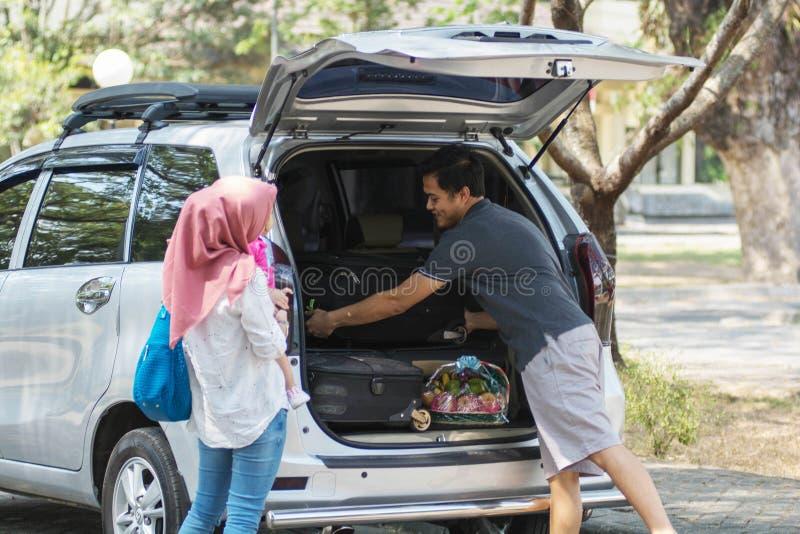Jonge moslimfamilie, vervoer, vrije tijd, wegreis en mensenconcept - gelukkig man, vrouw en meisje die klaar voor worden stock foto