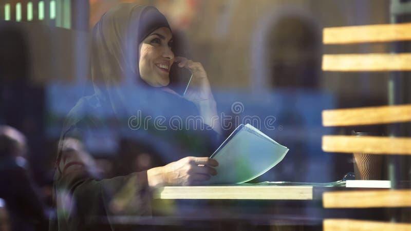 Jonge Moslimonderneemster in de documenten van de koffieholding, die op telefoon, gadget spreken royalty-vrije stock foto's