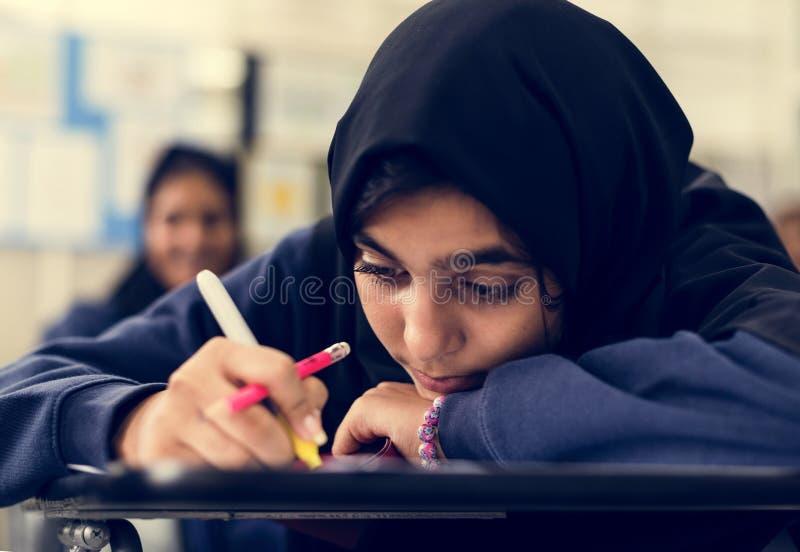 Jonge Moslimstudent die op school bestuderen royalty-vrije stock foto