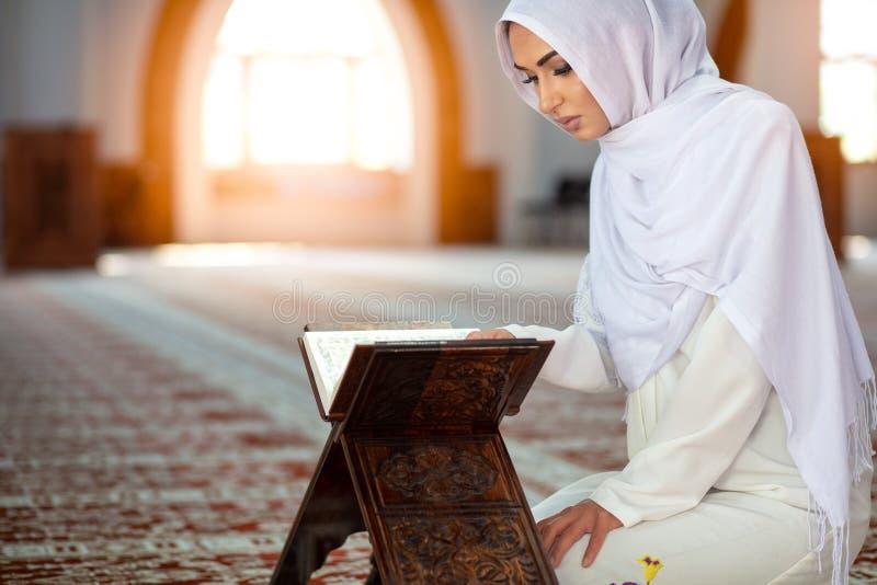 Jonge moslimvrouw die in moskee met quran bidden royalty-vrije stock afbeelding
