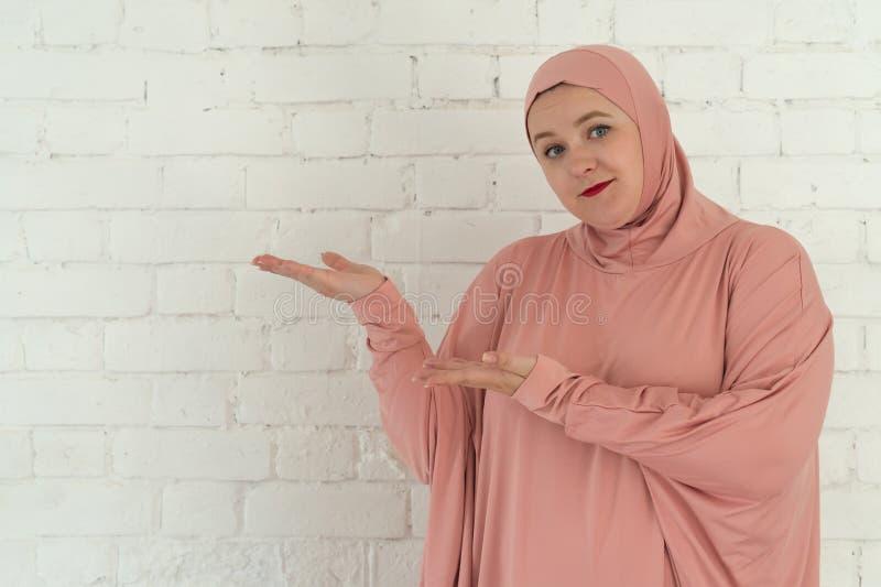 Jonge moslimvrouw in roze die hijabkleren op witte achtergrond wordt geïsoleerd Concept van de mensen het godsdienstige levenssti stock foto