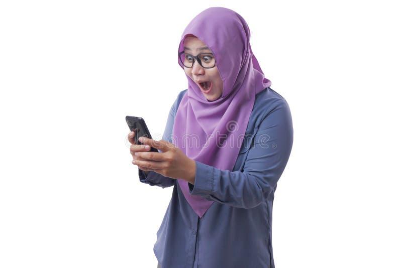 Jonge moslimvrouw wordt verrast door de schok en krijgt goed nieuws op haar telefoon stock foto's