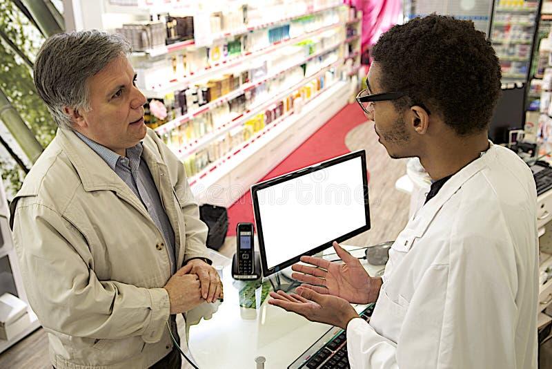Jonge Mulat mannelijke apotheker die met een klant spreken royalty-vrije stock foto's