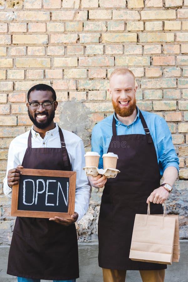 jonge multi-etnische baristas met teken open document zakken en beschikbare koffie vormt het glimlachen tot een kom stock afbeelding