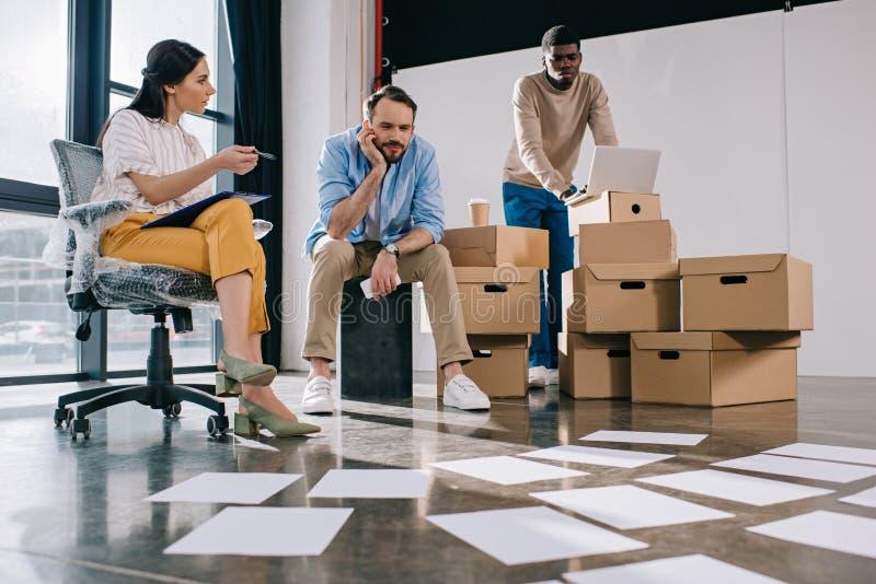 jonge multi-etnische bedrijfsmensen die documenten op vloer in nieuw bekijken stock foto