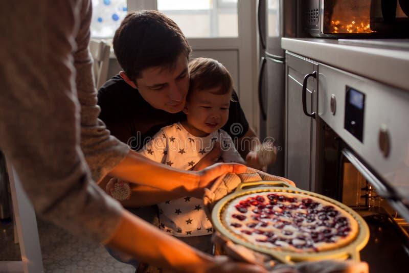 Jonge multi-etnische familie die een cake samen maken royalty-vrije stock foto's