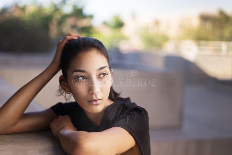Jonge multi etnische vrouw die aan kant kijken stock foto's