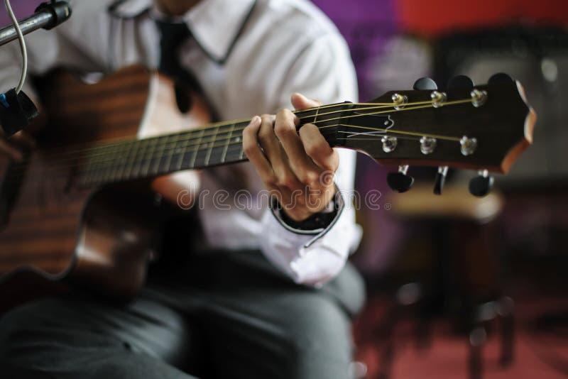 Jonge musicus die een gitaarsnaar op stadium houden stock afbeeldingen