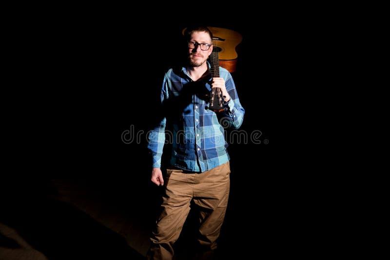 Jonge musicus die in plaidoverhemd een gitaar op zijn schouders over donkere achtergrond houden stock afbeeldingen
