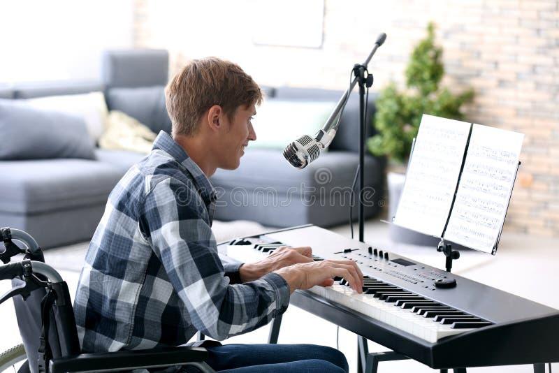Jonge musicus in rolstoel het spelen synthesizer thuis stock foto's