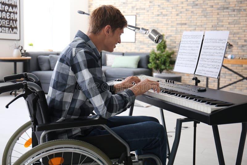 Jonge musicus in rolstoel het spelen synthesizer thuis royalty-vrije stock fotografie