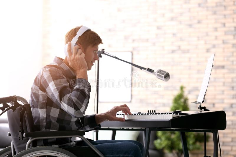 Jonge musicus in rolstoel het spelen synthesizer thuis royalty-vrije stock afbeelding