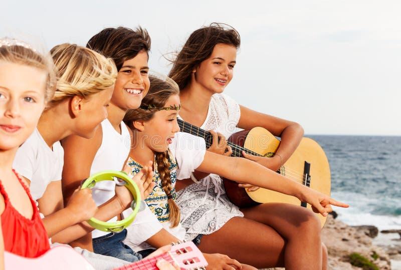 Jonge muziekband het spelen gitaar bij de kust royalty-vrije stock afbeelding