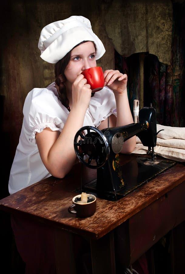 Jonge naaister met rode mok dichtbij oude naaiende mach royalty-vrije stock fotografie