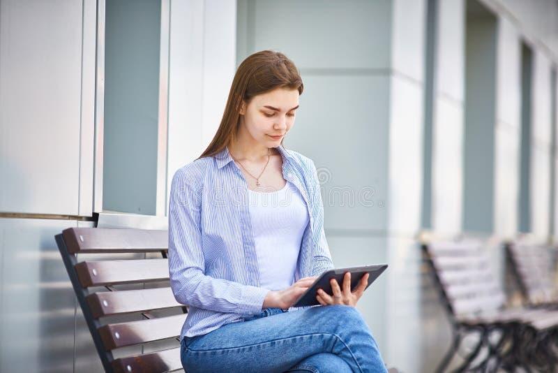 Jonge nadenkende meisjeszitting op een bank met een in hand tablet stock fotografie
