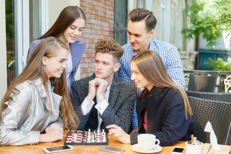 Jonge nadenkende vrienden die de schaakconcurrentie op een koffieachtergrond hebben Het concept van de vriendschap stock afbeeldingen