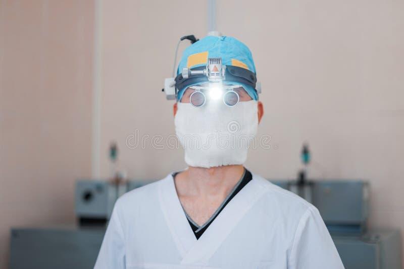Jonge neurochirurgenmens in glazen met binaire loupes voor microsurgery met licht in de werkende ruimte Moderne geneeskunde royalty-vrije stock afbeelding
