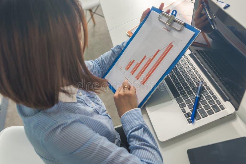 Jonge onderneemster in de blauwe financiële verslagen van de overhemdslezing in het bureau stock fotografie