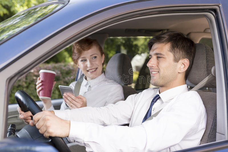 Jonge onderneemster die bij een taxibestuurder glimlachen stock afbeeldingen